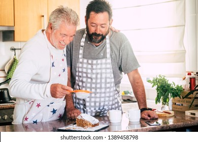 Family at home at work in the kitchen with senior mature father and adult son preparing a cake together like friends - diversity and mixed generations in the house