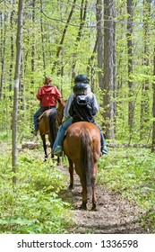 A family of horseback riders enjoys their day in the forest.