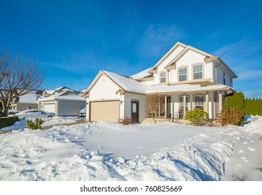 Family house with driveway and front yard in snow on winter sunny day. Luxury residential house with double garage on winter season