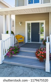 Family house entrance with yellow chair under the porch and decorative blossoming flowers