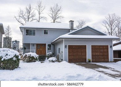 Family house with front yard and driveway in snow. Residential house on winter cloudy day