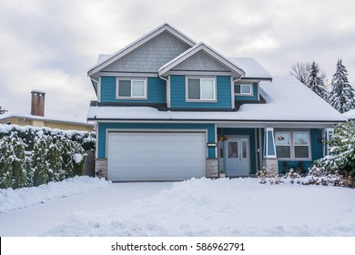 Family house with front yard in snow. Residential house on winter cloudy day