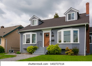 Family house with green lawn and decorative bushes in front.  Average residential house on cloudy day in British Columbia