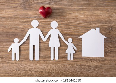 family with house model and heart on table