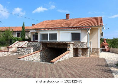 Family house with new exterior surrounded with stone tiles and large underground garage entrance in front with dense trees and cloudy blue sky in background