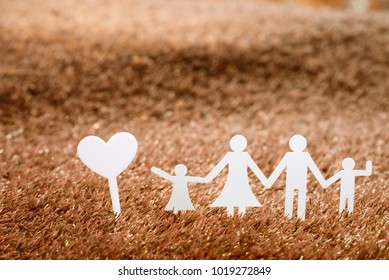 Family and house on green grass background,paper family concept.
