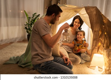 family, hygge and people concept - happy mother, father with lantern and little daughter with teddy bear playing in kids tent at night at home