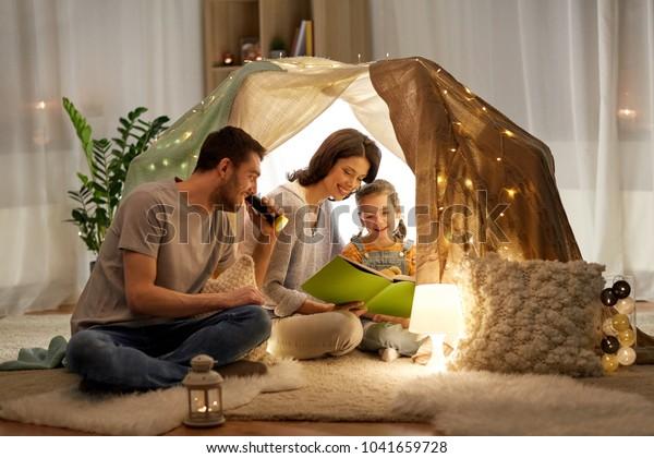 семья, hygge и люди концепция - счастливая мать, отец и маленькая дочь читают книгу с факелом в детской палатке ночью дома