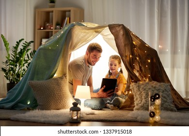 family, hygge and technology concept - happy father and little daughter with tablet pc computer in kids tent at night at home