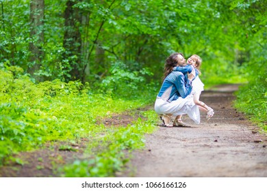 Family Ideas and Concepts. Happy Mother and Her Little Caucasian Daughter Posing Embraced Together In Green Summer Forest. Horizontal Image Composition