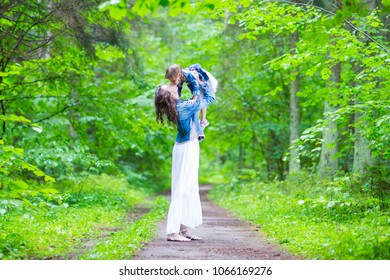 Family Ideas and Concepts. Happy Mother and Her Little Caucasian Daughter Posing with Kissing Expression Together In Green Summer Forest. Horizontal Image Composition