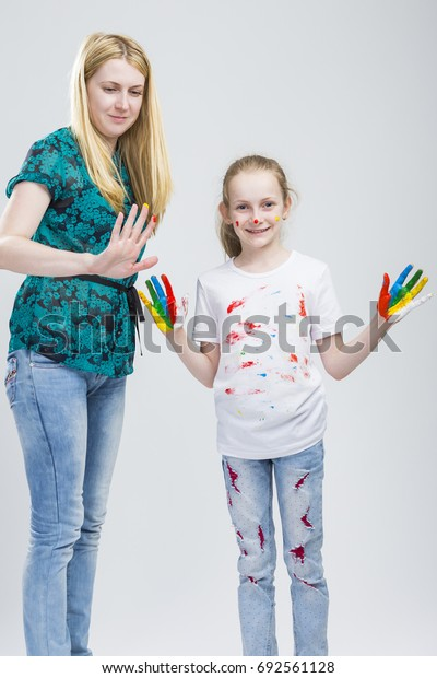 Family Ideas. Mother and Her LIttle Caucasian Blond Daughter Having Hand and Face Paint Time Together Indoors.Vertical Image Orientation