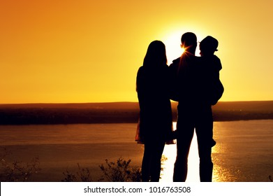 Family idyll. Silhouettes of mother, father and son standing together and admiring the sea during sunset in summer