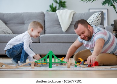 Family image of father and son playing on floor in toy road with cars
