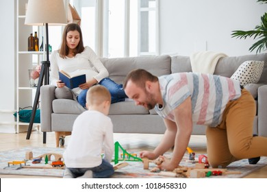 Family image of father and son playing on floor in toy road , pregnant woman reading book