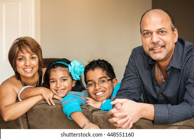 Family of Indian Origin smiling and looking at camera