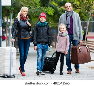 Family journey: happy spouses with children walking and luggage