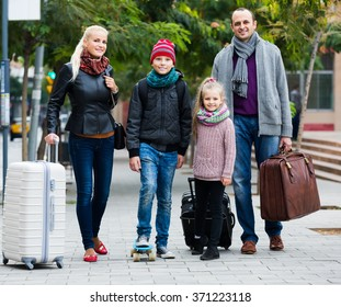 Family journey: spouses with children walking and luggage