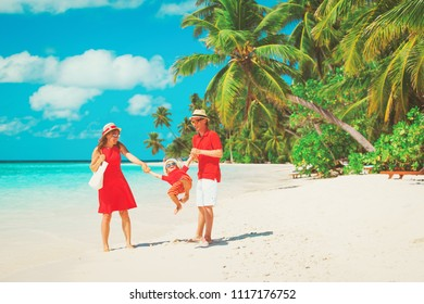 family with kid playing on tropical sand beach