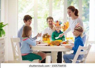 Family with kids eating Thanksgiving dinner. Roasted turkey and pumpkin pie on dining table with autumn decoration. Parents and children festive meal. Father and mother cutting meat. Paper crafts hat.