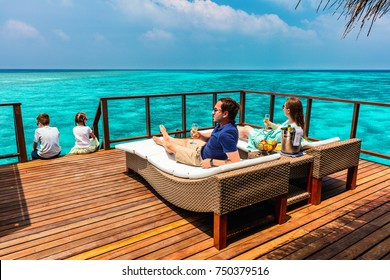 Family with kids enjoying tropical summer vacation relaxing at overwater villa in luxury resport