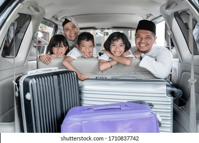 family and kids looking at the back of the trunk full with suitcase ready to go on holiday. mudik lebaran or balik kampung