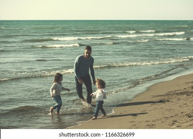 Family with kids resting and having fun at beach during autumn day filter