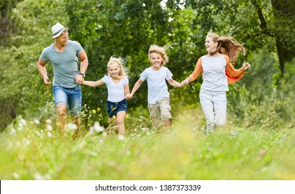 Family and kids run happily over a meadow in summer