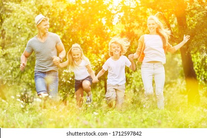 Family and kids run through a meadow in summer