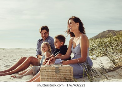 Family with kids sitting on the beach. Family having picnic on beach.