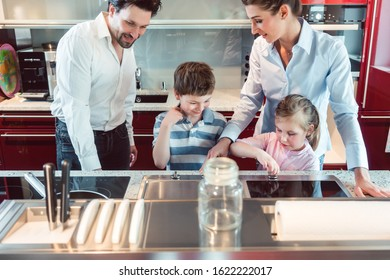 Family with kids testing a new kitchen they intend buying in the showroom