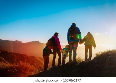 family with kids travel in mountains at sunset