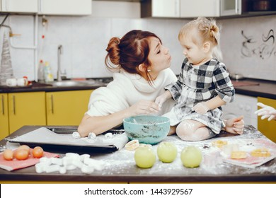 Family in a kitchen. Beautiful mother with little daughter