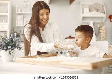 Family in a kitchen. Beautiful mother with little son. Flour on the table