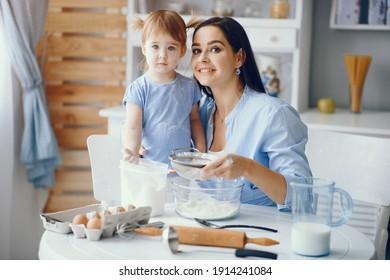 Familie in einer Küche. Schöne Mutter mit kleiner Tochter. Frau in blauem Hemd