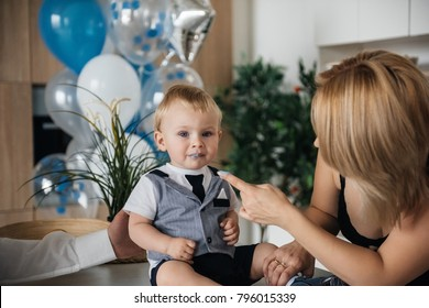 Family in the kitchen. The first birthday of the baby. The Celebration. White and blue balls. Mom, Dad and son spend time together. Try the cake.