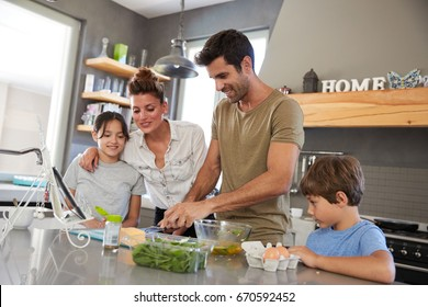 Family In Kitchen Following Recipe On Digital Tablet Together
