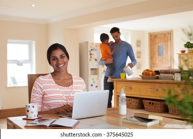 Family In Kitchen With Mother Using Laptop At Table