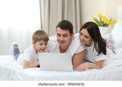 Family with laptop lying in bed