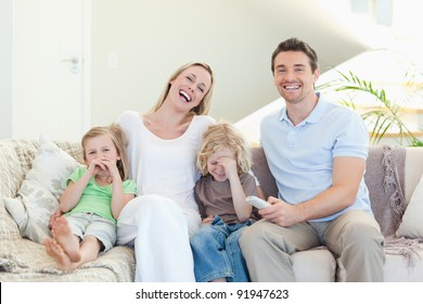 Family laughing on the sofa together