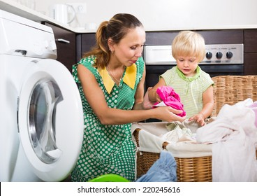 Family laundry. Happy woman with child putting clothes in to washing machine at home