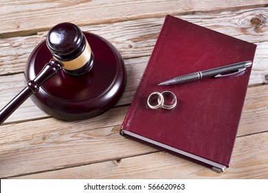 Family law concept. Gavel, rings and agenda on wooden table