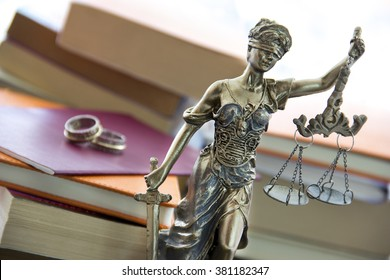Family law. Justice statue with sword and scale and marriage certificate