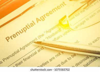 Family law, prenuptial agreement or contract entered into prior to marriage concept : Blue pen, a prenuptial agreement on a clipboard. Prenuptail agreement includes provisions for division of property