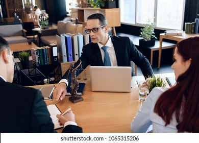 Family lawyer shows young couple where to sign agreement on divorce. Divorcing couple dissolves marriage contract. Couple going through divorce signing papers.