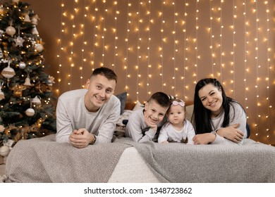 The family lays together on the bed and rejoices