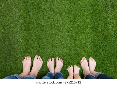 Family legs standing on green grass having fun outdoors in spring park.