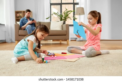 family, leisure and childhood concept - happy sisters doing arts and crafts at home