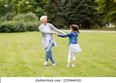 family, leisure and people concept - happy grandmother and granddaughter playing game or dancing at summer park