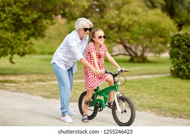 family, leisure and people concept - happy grandmother teaching granddaughter to ride bicycle at summer park